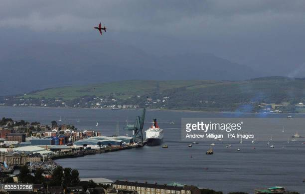 An aircraft from the Red Arrows performs a fly past of the QE2 which sits in the docks at Ocean Terminal in Greenock the ship is in Greenock for its...