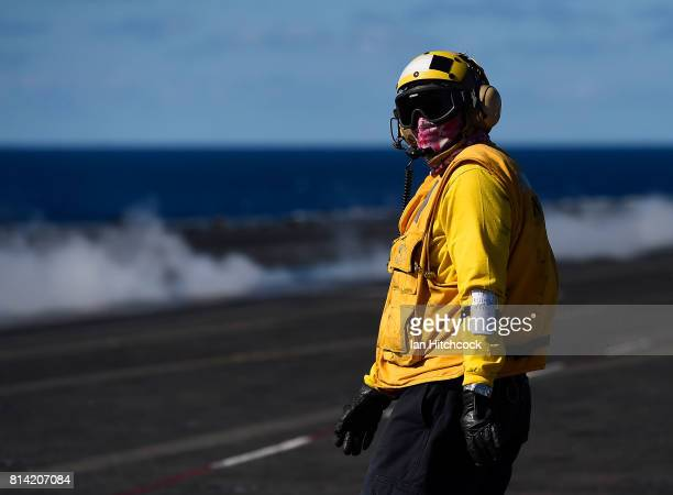An aircraft handler looks down the length of the deck after launching a Super Hornet during flight operations on July 14 2017 in Townsville Australia...