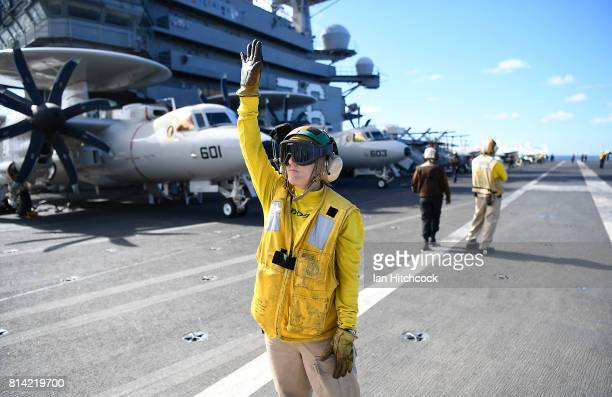 An aircraft handler signals during flight operations on July 14 2017 in Townsville Australia USS Ronald Reagan is a 1092 foot aircraft carrier which...