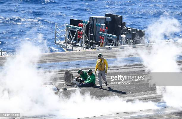 An aircraft handler walks back into position after launching a Super Hornet from the flight deck on July 14 2017 in Townsville Australia USS Ronald...