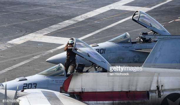 An aircraft maintainer is seen workng on a canopy of a Super Hornet on the deck of the USS Ronald Reagan on July 14 2017 in Townsville Australia USS...
