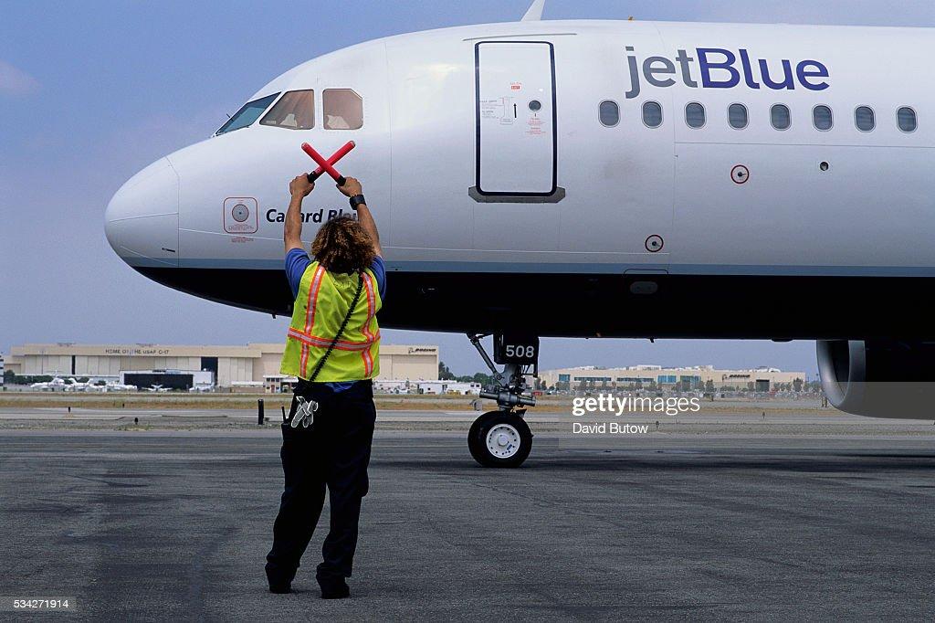 An aircraft maintenance crew personnel guides an arriving JetBlue flight on the tarmac at Long Beach Airport
