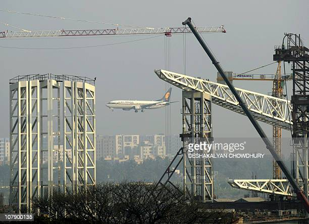 An aircraft of an Indian airline prepares to land beside a construction site at Netagi Subhash Chandra Bose Airport in Kolkata on January 6 2011 The...