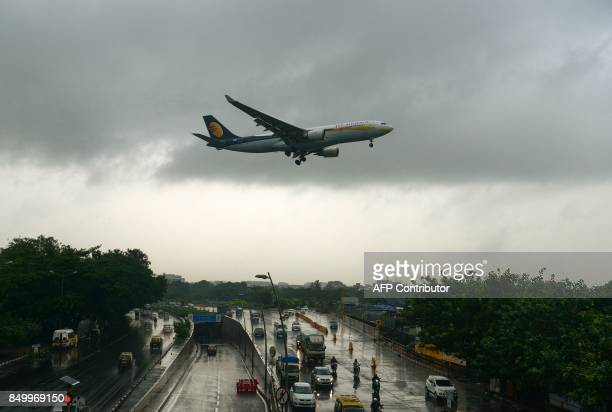An aircraft of India's Jet Airways lands during rain showers in Mumbai on September 20 2017 Dozens of flights were diverted from Mumbai after a...