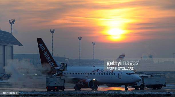An aircraft of the airline 'Air Berlin' is deiced at Duesseldorf International Airport on December 3 2010 in Duesseldorf Germany Heavy snowfalls...
