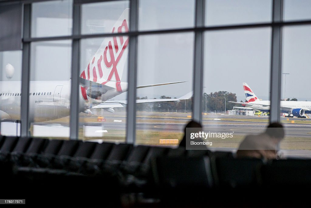 An aircraft operated by Virgin Australia Holdings Ltd. stands on the tarmac as passengers wait at a gate at the domestic terminal of Sydney Airport in Sydney, Australia, on Thursday, Aug. 29, 2013. Virgin will make a net loss in the range of A$95 million to A$110 million when it reports annual results tomorrow, the Brisbane-based carrier forecast Aug. 5. Photographer: Ian Waldie/Bloomberg via Getty Images