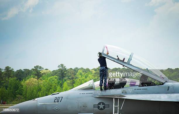 An aircrewman cleans the windshield on a F/A18 at Naval Air Station Oceana in Norfolk Virginia May 8 during the Department of Defense's tour deemed...