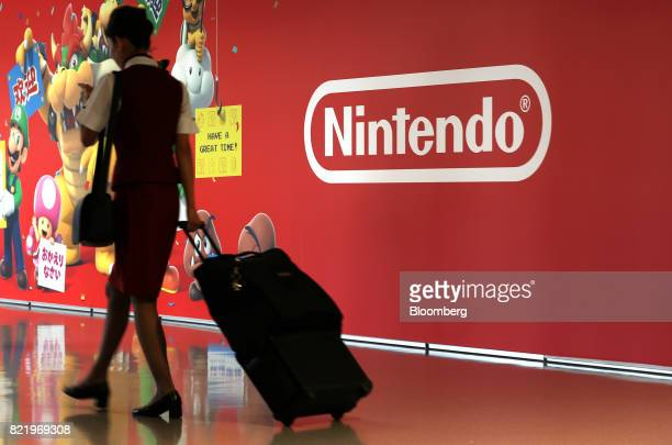 An airline employee walks past a mural featuring characters from Nintendo Co's Super Mario video games at Terminal 1 of Kansai International Airport...