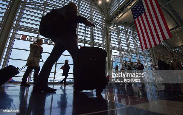 An airline travelers at Ronald Reagan National Airport walk to a Transportation Security Administration security checkpoint prior to traveling on...