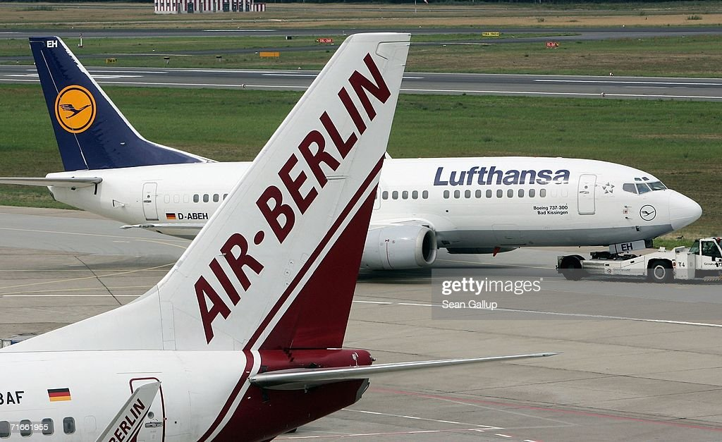 An airliner of German airline Lufthansa passes a plane of discounter Air Berlin August 17 2006 at Tegel Airport in Berlin Germany Air Berlin head...