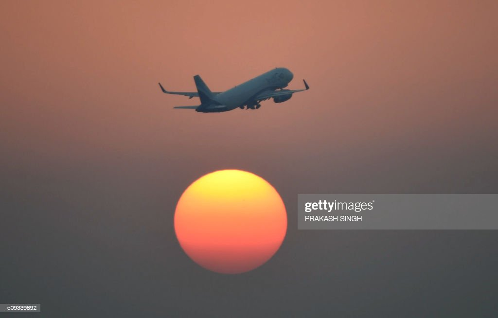 An airliner of India's IndiGo carrier flies over the setting sun in New Delhi on February 10, 2016. AFP PHOTO / Prakash SINGH / AFP / PRAKASH SINGH