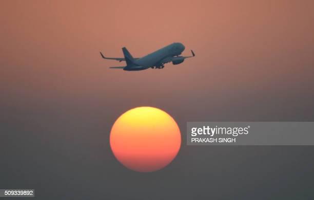 TOPSHOT An airliner of India's IndiGo carrier flies over the setting sun in New Delhi on February 10 2016 AFP PHOTO / Prakash SINGH / AFP / PRAKASH...
