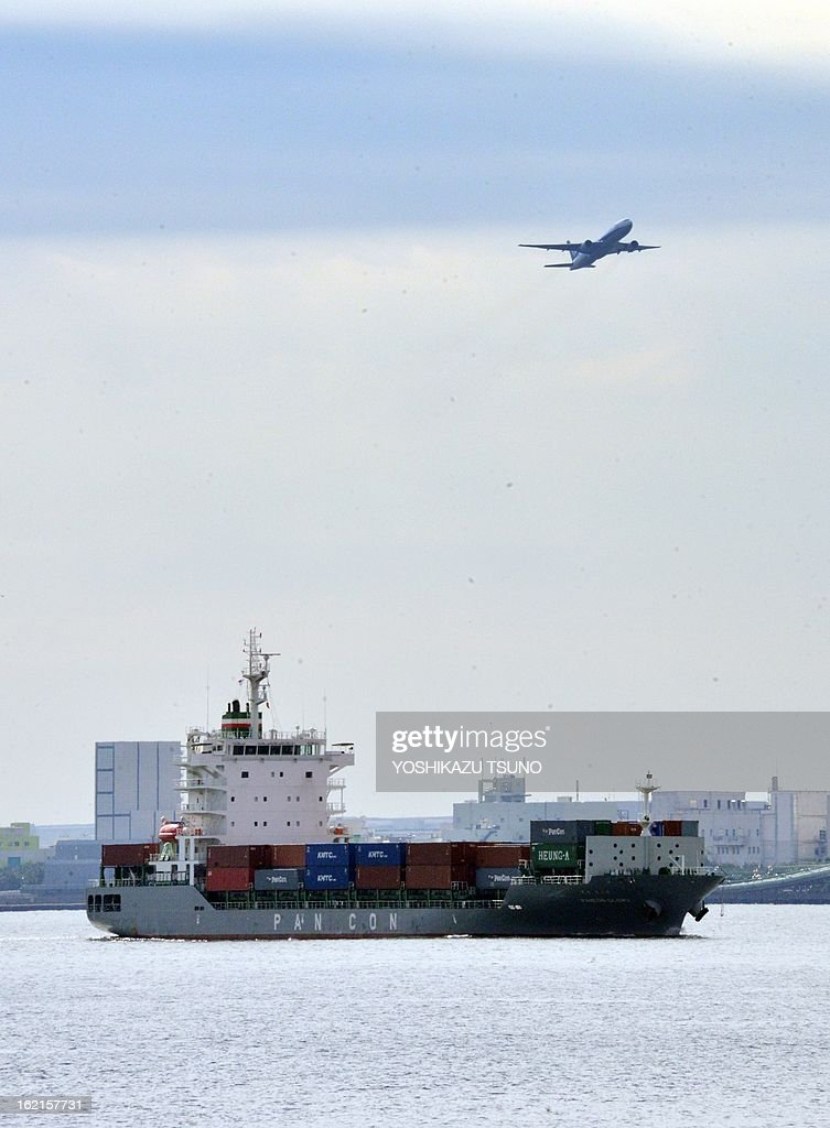 An airliner plane flies over a cargo at the Tokyo port on February 20, 2013. Japan logged its worst ever trade deficit for January due mainly to heavier fuel import bills. Finance ministry figures showed the economy suffered a shortfall of 1.63 trillion yen, the worst deficit on record for the month. AFP PHOTO / Yoshikazu TSUNO