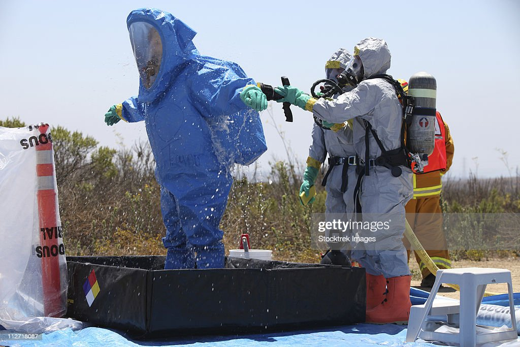An airman stands in a tub of cleaning solution during a decontamination process.