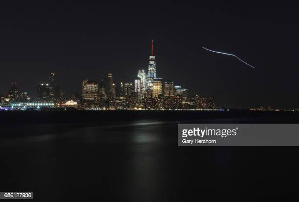 An airplane creates a streak in the sky behind One World Trade Center in New York City on May 18 as seen from Hoboken NJ