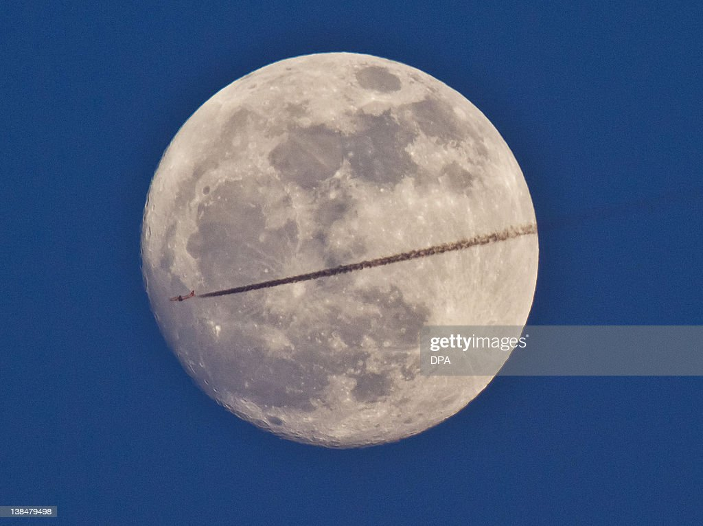 An airplane drawing a contrail seems to divide the full moon in two halves on February 6, 2012 in the sky over Frankfurt/M., western Germany.