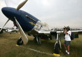 An airplane enthusiast takes photos of a World War IIera P51 Mustang during the Experimental Aircraft Association's 2007 AirVenture annual flyin and...
