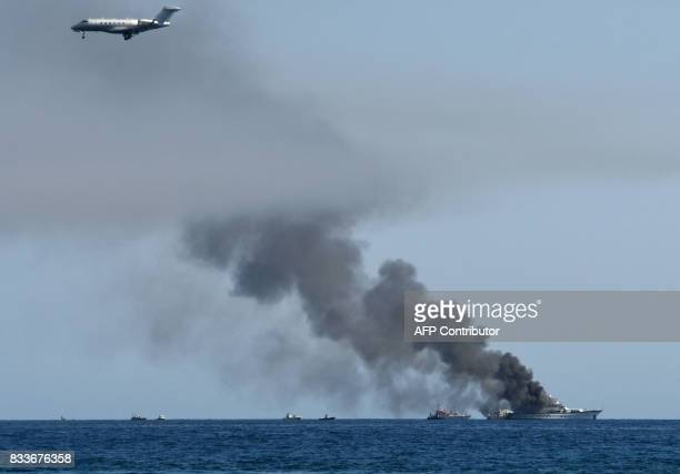 An airplane flies above as smoke rises from the boat 'If Only' a 39meterlong yacht that is on fire off SaintLaurentduVar near Nice southern France on...