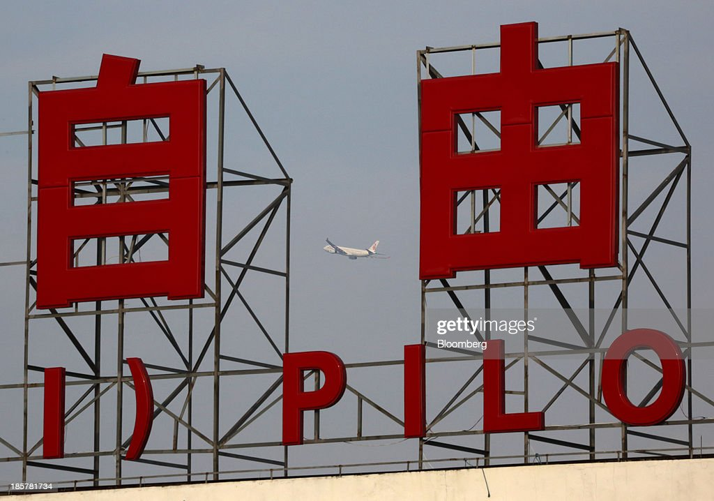 An airplane flies behind a sign for China (Shanghai) Pilot Free Trade Zone's Pudong free trade zone in Shanghai, China, on Thursday, Oct. 24, 2013. The area is a testing ground for free-market policies that Premier Li Keqiang has signaled he may later implement more broadly in the world's second-largest economy. Photographer: Tomohiro Ohsumi/Bloomberg via Getty Images