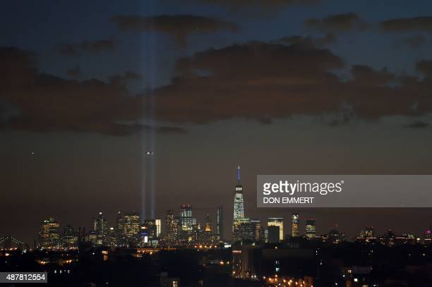 An airplane flies in front of the Tribute in Light over lower Manhattan September 11 2015 in New York The lights will shine for one night as a...