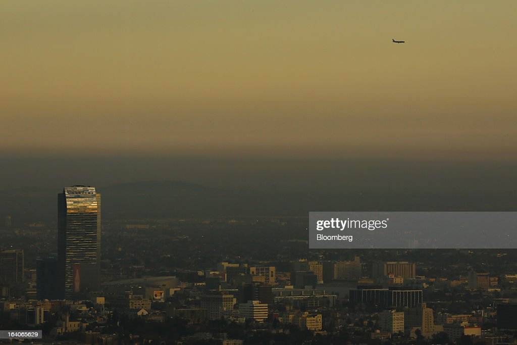 An airplane flies over AEG's LA Live development with the Ritz Carlton Hotel and Staples Center at sunset in Los Angeles, California, U.S., on on Thursday, March 14, 2013. California should start a state-run bank to finance economic development that's less polluting and more environmentally friendly, financed by auctions of greenhouse-gas carbon credits, Lieutenant Governor Gavin Newsom said. Photographer: Patrick T. Fallon/Bloomberg via Getty Images