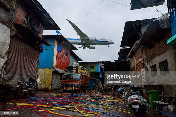 An airplane flies very close above an residential area near Santa Cruz airport
