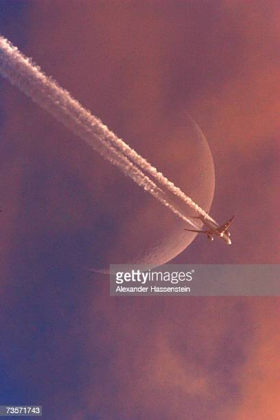 An airplane leaves a vapor trail as it flies in front of he moon on January 17 2007 above Hanover Germany Germany is currently in a heated debate...