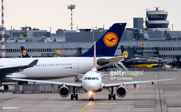 An airplane operated by German airline Air Berlin rolls on the tarmac past a Lufthansa plane on October 10 2017 at Duesseldorf airport western...