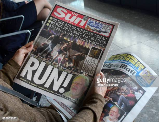 An airplane passenger waiting to board a flight at Heathrow International Airport in London England reads copies of two English tabloid newspapers...