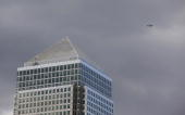 An airplane passes over One Canada Square at the Canary Wharf development in London UK on Wednesday July 28 2010 Office rents in Canary Wharf the...