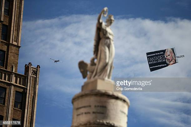 An airplane pulls a banner advertising a new night club flys past the Battle Monument during the Star Spangled Spectacular September 12 2014 in...