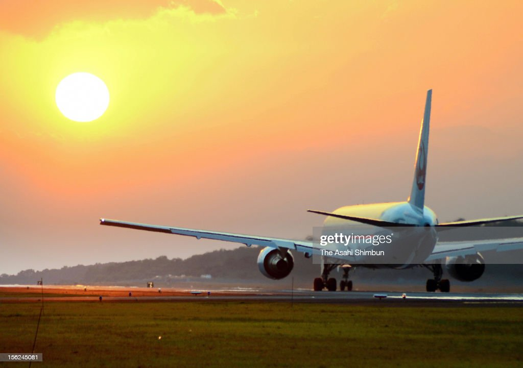 An airplane takes off toward the setting sun at Kumamoto Airport on November 6, 2012 in Ozu, Kumamoto, Japan. The airport, having the runway spreading from east to west and the sun setting the west edge of the runway mid to end of November, attracts many amateur photographers and airplane fans at the airport this time of the season to shoot the scene.