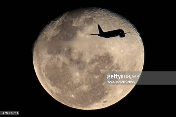 An airplane taking off from Santos Dumont airport in Rio de Janeiro flies in front of the moon on June 4 2015 AFP PHOTO / YASUYOSHI CHIBA