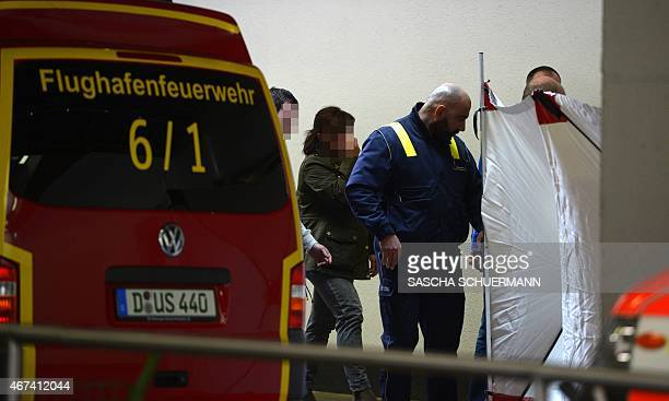 An airport employee accompanies people towards a protected area reserved for relatives of the Germanwings plane crash victims on March 24 2015 at the...