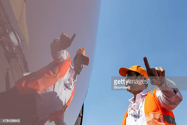 An airport employee is reflected in a Dassault Aviation SA Falcon 7X aircraft on display during the India Aviation 2014 air show held at the Begumpet...