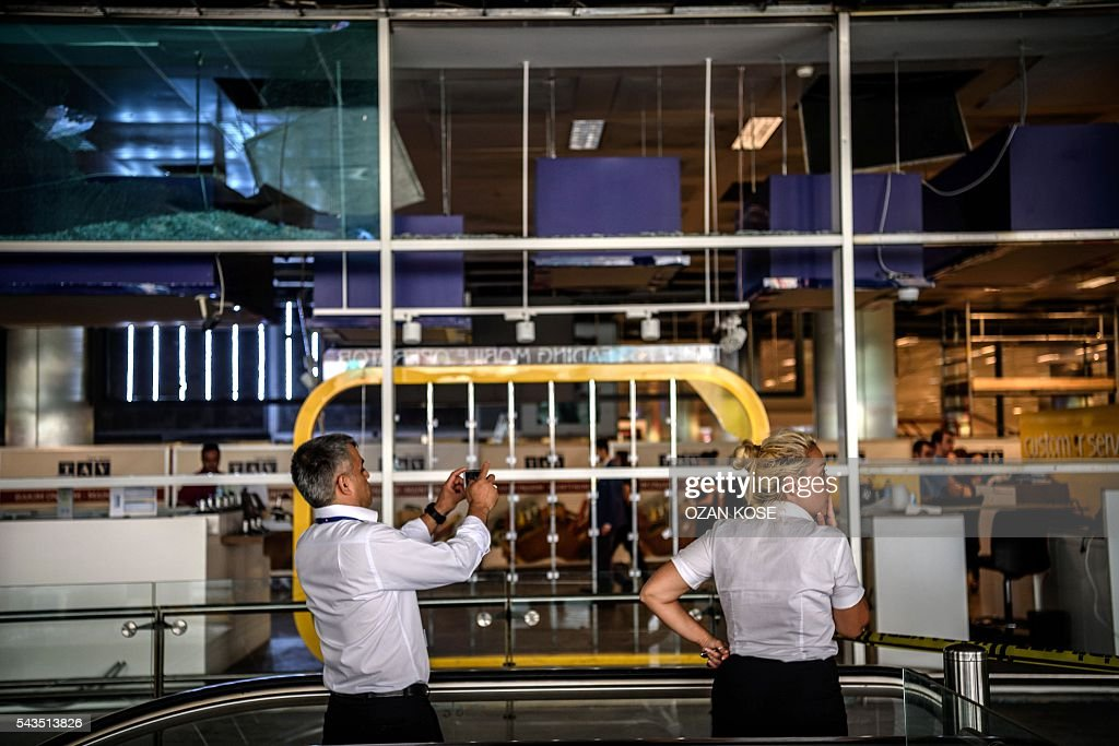 An airport employee takes pictures of broken windows at the attacks and explosions site in Ataturk airport's international arrivals terminal on June 29, 2016, a day after a suicide bombing and gun attack targeted Istanbul's airport, killing at least 36 people. A triple suicide bombing and gun attack that occurred on June 28, 2016 at Istanbul's Ataturk airport has killed at least 36 people, including foreigners, with Turkey's prime minister saying early signs pointed to an assault by the Islamic State group. / AFP / OZAN