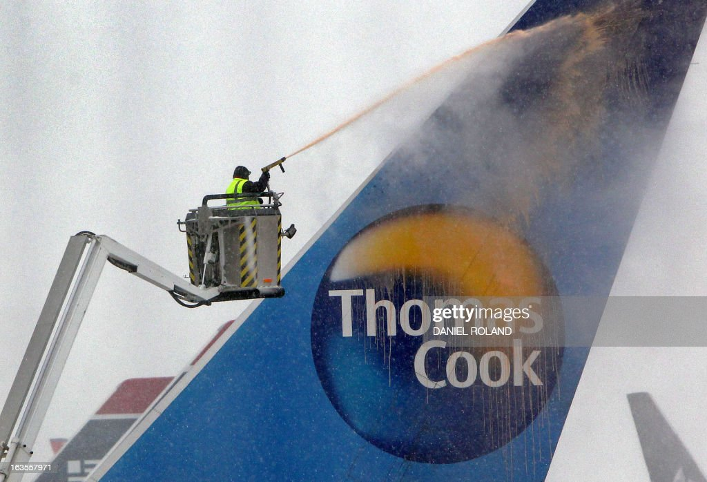 An airport employee uses a de-icing engine to defrost a Thomas Cook airplane on the snow covered ground of the airport in Frankfurt am Main, western Germany, on March 12, 2013 as the Europe's third-busiest hub was able to re-open one runway for takeoffs only on the afternoon, after being forced to close completely due to heavy snow.. ROLAND