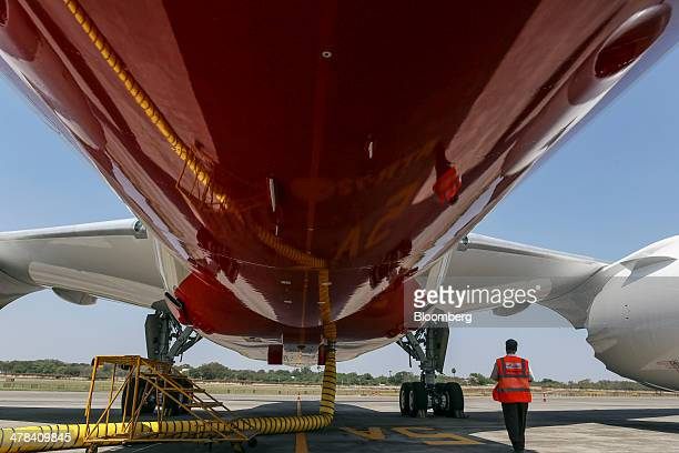 An airport employee walks below a Boeing Co 787 Dreamliner aircraft operated by Air India Ltd as it sits on display during the India Aviation 2014...
