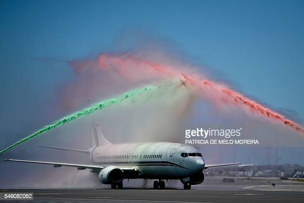 TOPSHOT An airport firefighter's unit spray water in the national colours over the aircraft carrying Portugal's national football team members during...