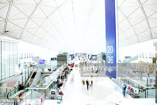 An airport interior, people travelling, motion blurred and high key