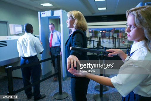 An airport security officer uses a hand held metal detector to check a traveler as another traveler walks through a metal detector in the background.,