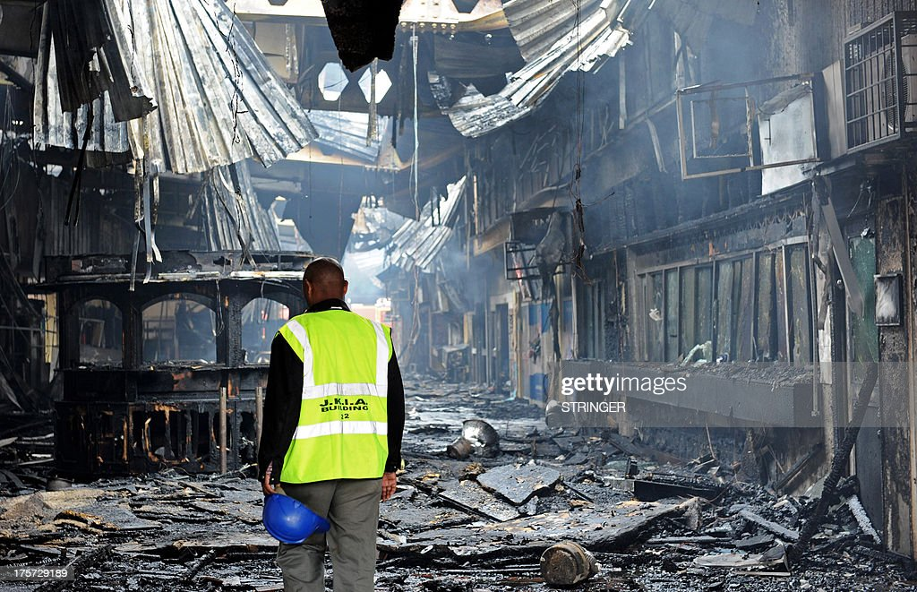 An airport staff employee stands among the debris after a fire damaged a terminal at the Jomo Kenyatta international airport in Nairobi on August 7, 2013. A massive fire shut down Nairobi's international airport on Wednesday with flights diverted to regional cities as firefighters battled to put out the blaze in east Africa's biggest transport hub. Dramatic plumes of black smoke billowed out of the main arrivals terminal, but by 9.00 am (0600GMT), some four hours after the blaze broke out, firefighters had succeeded in stemming the raging flames. AFP PHOTO /Stringer