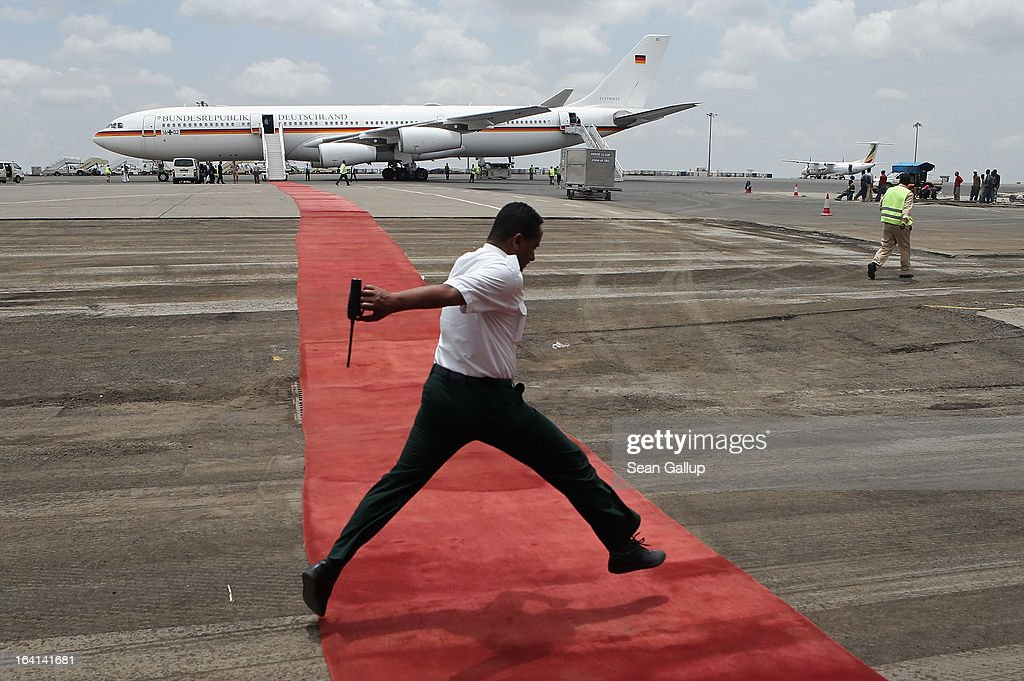 An airport technician jumps across the red carpet leading the German presidential plane prior to the departure of German President Joachim Gauck at Bole International Airport on March 20, 2013 in Addis Ababa, Ethiopia. President Gauck and First Lady Daniela Schadt were in Ethiopia for a four-day state visit.