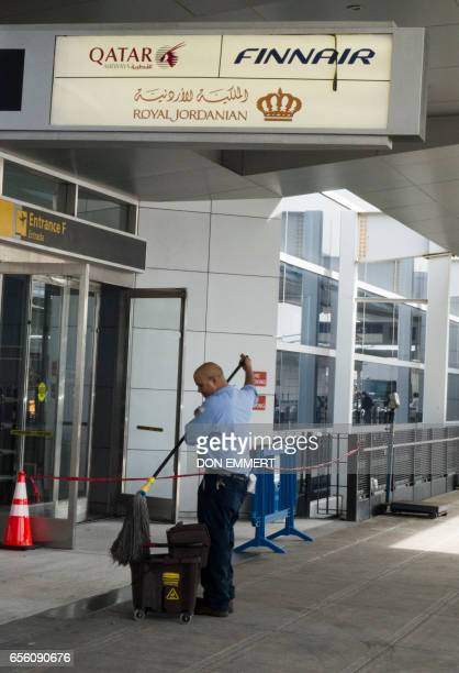 An airport worker cleans up outside the terminal of Qatar Airways Royal Jordanian Airlines and Finnair on March 21 2017 at John F Kennedy...
