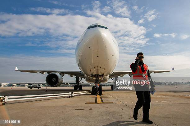 An airport worker speaks on a radio beside a TAP SGPS SA Airbus A330223 airliner at Lisbon International airport operated by ANAAeroportos de...