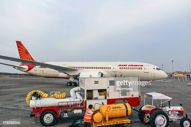 An airport worker stands next to a diesel tank as a Boeing Co 787 Dreamliner aircraft operated by Air India Ltd stands on display during the India...
