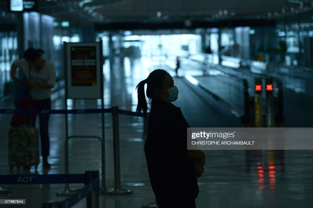 An Airports of Thailand employee wears a face mask as she waits for travelers to walk past a thermoscan checking their body temperature on arrival at...