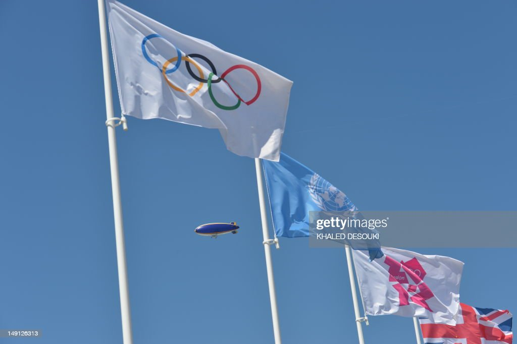 An airship fly monitoring over the Olympic village is pictured next to the Olympic flag during the flag raising ceremony at the Olympic village in London on July 23, 2012, four days before the start of the London 2012 Olympic Games.