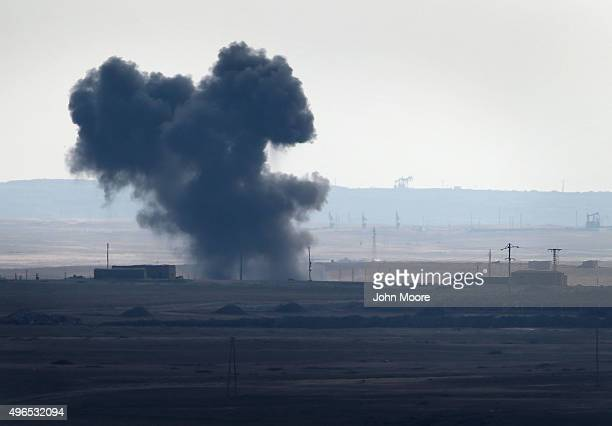 An airstrike by a US led coalition warplane explodes on an ISIL position on November 10 2015 near the ISILheld town of Hole Rojava Syria Troops from...