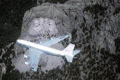 An airtoair overhead view of a 4th Airborne Command and Control Squadron EC135 Stratolifted aircraft over Mount Rushmore